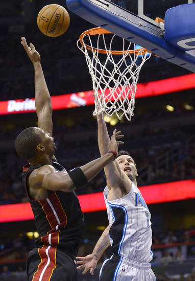 Orlando Magic guard J.J. Redick, right, puts up a shot in front of Miami Heat forward Chris Bosh during the first half of an NBA basketball game in Orlando, Fla., Monday, Dec. 31, 2012. (AP Photo/Phelan M. Ebenhack)