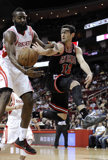 Chicago Bulls' Kirk Hinrich (12) tries to pass the ball around Houston Rockets' James Harden during the first half of an NBA basketball game Wednesday, Nov. 21, 2012, in Houston. (AP Photo/Pat Sullivan)