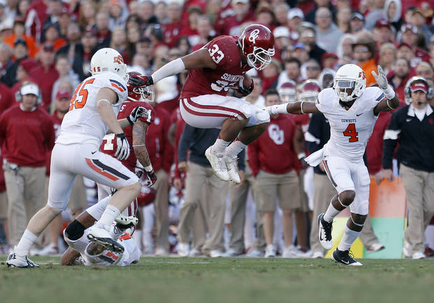 Oklahoma's Trey Millard (33) leaps in between Oklahoma State's Caleb Lavey (45) and Justin Gilbert (4) during the Bedlam college football game between the University of Oklahoma Sooners (OU) and the Oklahoma State University Cowboys (OSU) at Gaylord Family-Oklahoma Memorial Stadium in Norman, Okla., Saturday, Nov. 24, 2012. Photo by, Sarah Phipps The Oklahoman