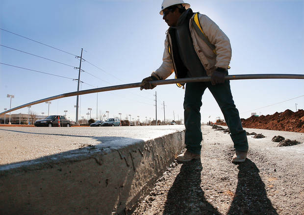 A construction worker evens out concrete  as progress is made on the $30 million  reconstruction project.  PHOTO BY JIM BECKEL, THE OKLAHOMAN
