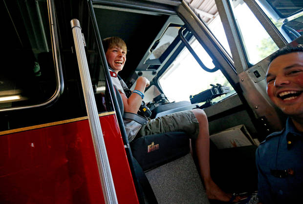 Cancer patient Sam Oliver, 13, from London, laughs with Warr Acres firefighter Tony Peevyhouse after Oliver set of an alarm as he sat down inside the fire truck for a ride. Photo by Bryan Terry, The Oklahoman