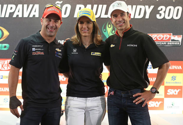 Brazilian IndyCar drivers, from left, Tony Kanaan, Ana Beatriz Figueiredo and Helio Castroneve pose for pictures at a news conference in Sao Paulo, Brazil, Thursday, May 2, 2013.  Brazil will host the 4th race of the Indy Car season on May 5. (AP Photo/Andre Penner)