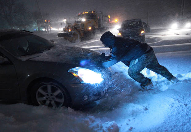 A man tries to push a vehicle that got stuck on Route 347 in Lake Grove, N.Y. early Saturday morning, Feb, 9, 2013. Dozens of vehicles remain stranded on this stretch of Long Island road. (AP Photo/Newsday, John Paraskevas) ORG XMIT: NYANE501