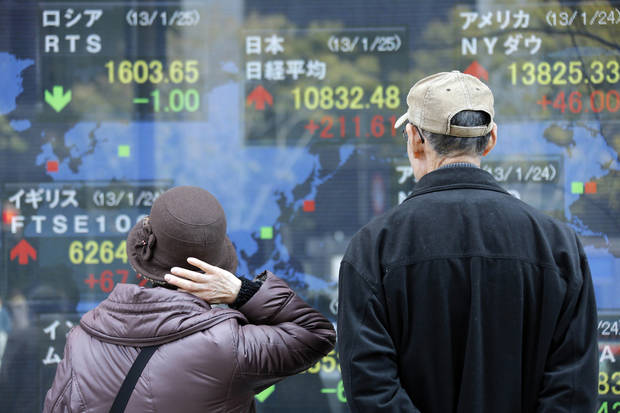 Pedestrians look at an electronic stock board of a securities firm in Tokyo, Friday, Jan. 25, 2013.  Japan�s benchmark stock index jumped about 2 percent Friday after the country�s currency continued to slide against the dollar. (AP Photo/Koji Sasahara)