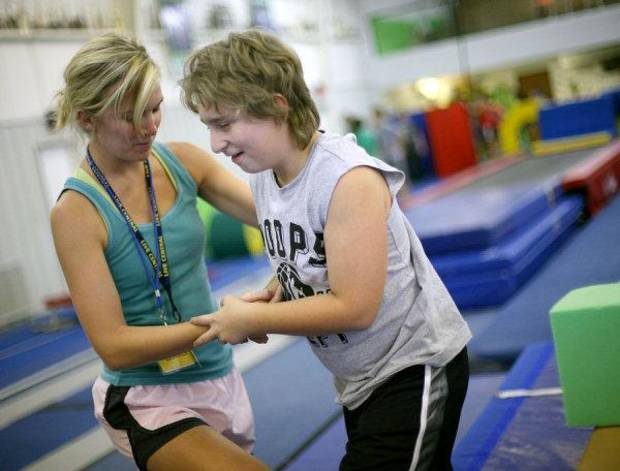 Seth Wedel, right, of Jenks, gets help around a balance beam from Gloria Hill, a camp counselor at Mat Trotters Gymnastics in Oklahoma City on Wednesday during the Oklahomans Without Limits summer camp. PHOTO BY JOHN CLANTON, THE OKLAHOMAN <strong>JOHN CLANTON - John Clanton</strong>