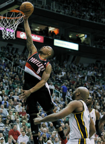 Portland Trail Blazers guard Damian Lillard (0) goes to the basket with a layup above Utah Jazz guard Jamaal Tinsley, right, in the first half during an NBA basketball game on Friday, Feb. 1, 2013, in Salt Lake City. (AP Photo/Steve C. Wilson)