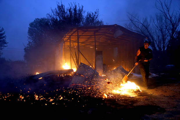 Tommy Green tries to put out hot spots near his burned storage building next to his home in Luther, Okla., after wildfire moved through the area on Friday, August 3, 2012. Photo by Bryan Terry, The Oklahoman
