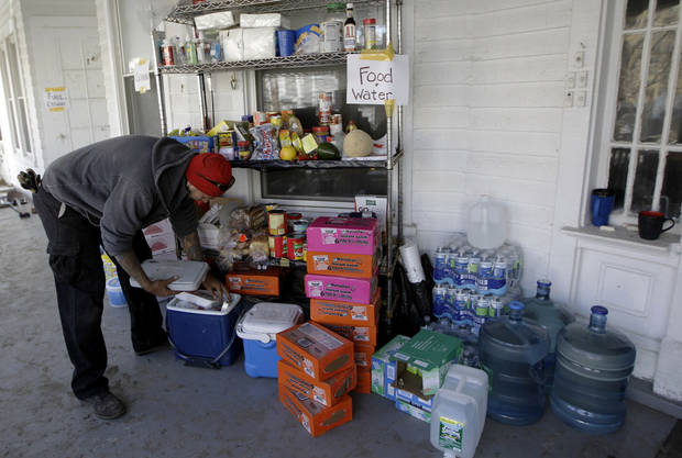 Tim Hill puts donated items for distribution on his front porch in the Rockaways section of New York, Saturday, Nov. 3, 2012.  More New Yorkers awoke Saturday to power being restored for the first time since Superstorm Sandy pummeled the region, but patience wore thin among those in the region who have been without power for most of the week.  (AP Photo/Kathy Willens) ORG XMIT: NYKW115
