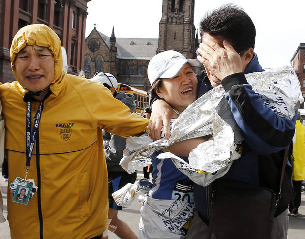An unidentified Boston Marathon runner, center, is reunited with loved ones near Copley Square following an explosion in Boston Monday, April 15, 2013. (AP Photo/Winslow Townson) ORG XMIT: MAWT102
