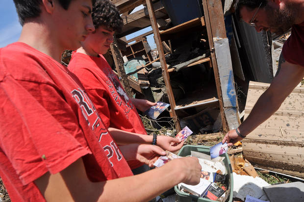 Brian Roberts,14, (left) and Caden Powell, 13, (middle) show Michael Roberts (right) photos that they pulled from a tub in a ruined storage shed in their back yard. Photo by KT King, The Oklahoman
