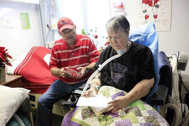 Ed Hutchison opens a Christmas present for his wife, Glenda Kay, in her room at Kindred Hospital in Oklahoma City. Photo by SARAH PHIPPS, the Oklahoman