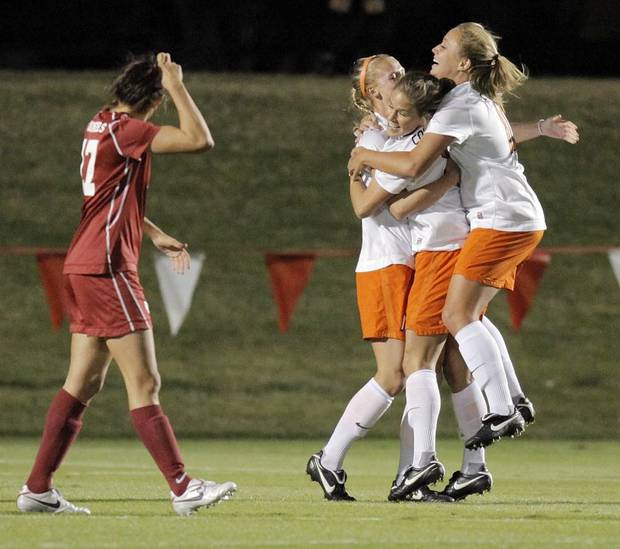 WOMEN'S COLLEGE SOCCER / UNIVERSITY OF OKLAHOMA / OKLAHOMA STATE UNIVERSITY: From right, OSU's Taylor Mathews (10), Kyndall Treadwell (5) and Megan Marchesano (16) celebrate a goal by Marchesano as OU's Samantha Howell (17) walks by in the first half of the Bedlam women's soccer game between Oklahoma State and Oklahoma at John Crain Field in Norman, Okla., Friday, October 29, 2010. Photo by Nate Billings, The Oklahoman ORG XMIT: KOD