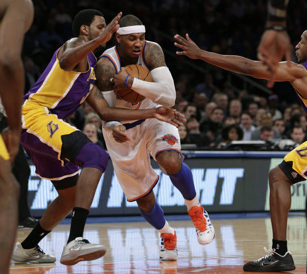 New York Knicks forward Carmelo Anthony (7) protects the ball as he drives past Los Angeles Lakers forward Devin Ebanks (3) in the first half of their NBA basketball game at Madison Square Garden in New York, Thursday, Dec. 13, 2012.  (AP Photo/Kathy Willens)