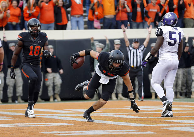 Oklahoma State's Charlie Moore (17) celebrates his touchdown with Blake Jackson (18) in front of TCU's Kenny Cain (51) during a college football game between Oklahoma State University (OSU) and Texas Christian University (TCU) at Boone Pickens Stadium in Stillwater, Okla., Saturday, Oct. 27, 2012. Photo by Sarah Phipps, The Oklahoman