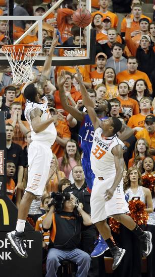 Oklahoma State &#039;s Michael Cobbins (20) and Marcus Smart (33) defend on Kansas&#039; Elijah Johnson (15) during the college basketball game between the Oklahoma State University Cowboys (OSU) and the University of Kanas Jayhawks (KU) at Gallagher-Iba Arena on Wednesday, Feb. 20, 2013, in Stillwater, Okla. Photo by Chris Landsberger, The Oklahoman