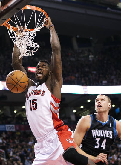 CORRECTS RAPTORS PLAYER TO AMIR JOHNSON, NOT ED DAVIS - Toronto Raptors' Amir Johnson, left, dunks past Minnesota Timberwolves center Greg Stiemsma (34) during the first half of their NBA basketball game, Sunday, Nov. 4, 2012, in Toronto. (AP Photo/The Canadian Press, Nathan Denette)