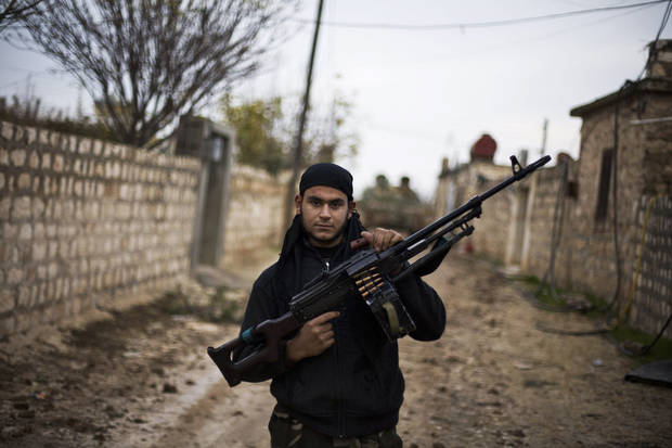 In this Wednesday, Dec. 12, 2012 photo, a Free Syrian Army fighter poses as he carries his weapon in the northern province of Aleppo, Syria. Syria's civil war has killed more than 40,000 people. (AP Photo/Manu Brabo)