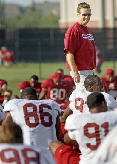 OU football coach Bob Stoops talks with his players before practice Thursday in Norman. Stoops gave the fans in attendance a hard time when he didn't think they were cheering enough for non-offensive players. PHOTO BY BRYAN TERRY, THE OKLAHOMAN
