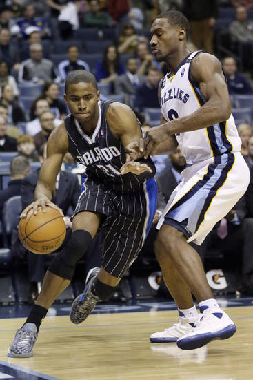 Orlando Magic's Moe Harkless (21) moves the ball past Memphis Grizzlies' Darrell Arthur during the first half of an NBA basketball game in Memphis, Tenn., Friday, Feb. 22, 2013. (AP Photo/Danny Johnston)