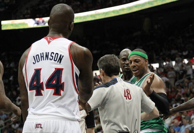 An official step between Atlanta Hawks forward Ivan Johnson (44) and Boston Celtics forward Paul Pierce after Pierce was fouled in the second half of Game 2 of an NBA first-round playoff series basketball series Tuesday, May 1, 2012, in Atlanta. Boston won 87-80 and evened the series at one game each. (AP Photo/John Bazemore)