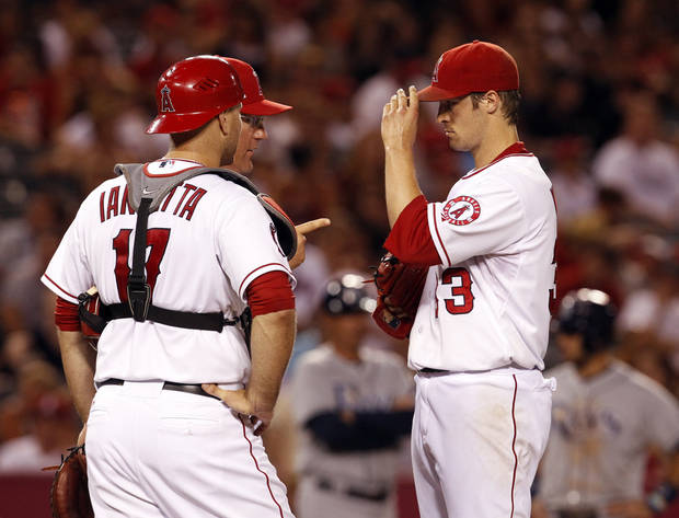 Los Angeles Angels pitching coach Mike Butcher and catcher Chris Iannetta make a visit to starting pitcher C.J. Wilson in the fifth inning of a baseball game against the Tampa Bay Rays in Anaheim, Calif., on Saturday, Aug. 18, 2012. (AP Photo/Christine Cotter)