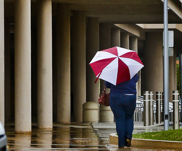 A pedestrian walks with an umbrella in downtown Oklahoma City on Wednesday, April 10, 2013, in Oklahoma City, Okla.  Photo by Chris Landsberger, The Oklahoman