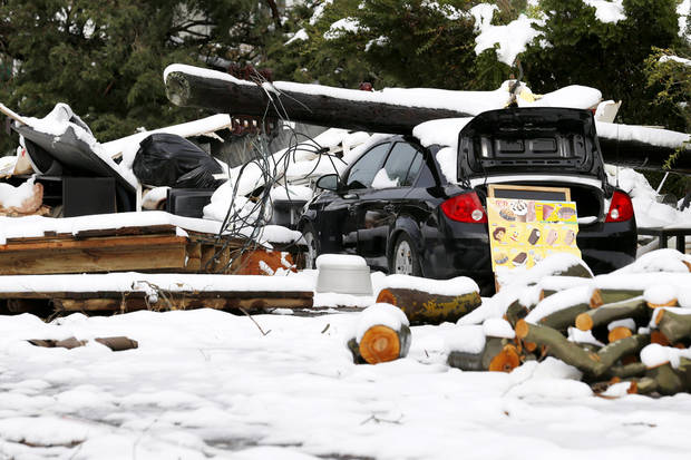 A down power poll rests on top of a vehicle as snow covered debris from Superstorm Sandy lay in the middle of a street following a nor'easter storm, Thursday, Nov. 8, 2012, in Point Pleasant, N.J.  The New York-New Jersey region woke up to wet snow and more power outages Thursday after the nor'easter pushed back efforts to recover from Superstorm Sandy, that left millions powerless and dozens dead last week. (AP Photo/Julio Cortez) ORG XMIT: NJJC115