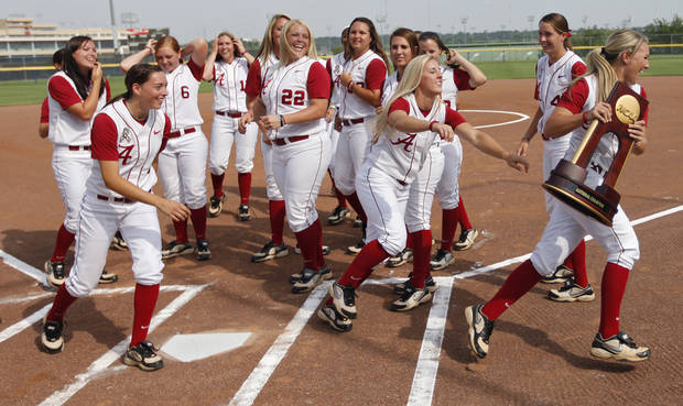 University of Alabama's Whitney Larsen, right, acts like she is going to take off with the NCAA national championship trophy during the Women's College World Series of softball practice and media day at ASA Hall of Fame Stadium on, Wednesday, June 1, 2011. Photo by Chris Landsberger, The Oklahoman