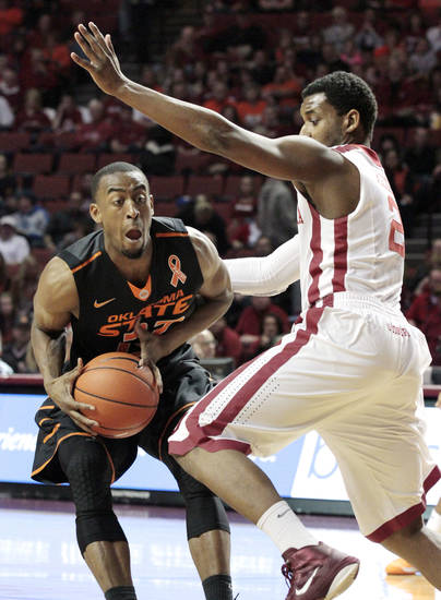 Cowboy's Markel Brown (22) looks to pass around Sooner's Steven Pledger (2) as the University of Oklahoma Sooners (OU) play the Oklahoma State Cowboys (OSU) in NCAA, men's college basketball at The Lloyd Noble Center on Saturday, Jan. 12, 2013  in Norman, Okla. Photo by Steve Sisney, The Oklahoman