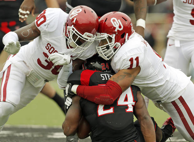 OU's R.J. Washington (11) collides with Javon Harris (30) as he brings down Texas Tech's Erich Stephens Jr. (24) during a college football game between the University of Oklahoma (OU) and Texas Tech University at Jones AT&T Stadium in Lubbock, Texas, Saturday, Oct. 6, 2012. Photo by Nate Billings, The Oklahoman