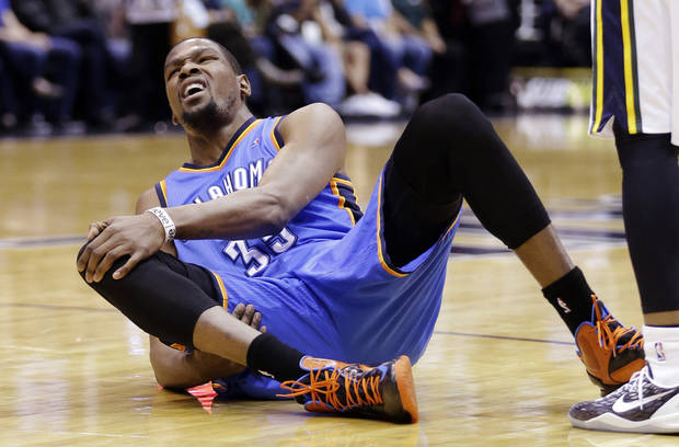 Oklahoma City Thunder's Kevin Durant (35) grabs his knee after falling in the first quarter during an NBA basketball game against the Utah Jazz, Tuesday, April 9, 2013, in Salt Lake City. (AP Photo/Rick Bowmer) ORG XMIT: UTRB107