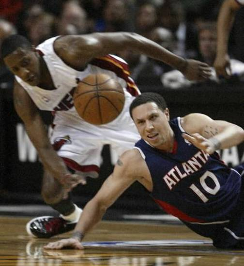 Atlanta Hawks guard  Mike  Bibby (10) attempts to regain control of a loose ball against Miami Heat guard Mario Chalmers during the first quarter of Game 4 of a first-round Eastern Conference NBA playoff basketball series Monday, April 27, 2009, in Miami. (AP Photo/Wilfredo Lee) 