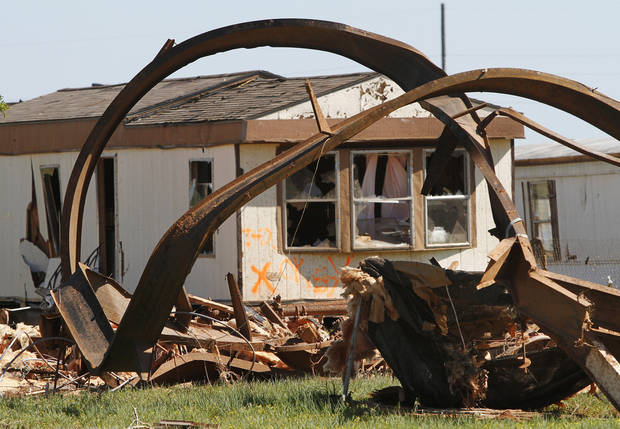 Twisted metal from the base of a trailer home frames a damaged home in the background. Nine trailers were destroyed  and many others received major damage in the Hide-A-Way Mobile Home Park when a  killer tornado roared through sections of Woodward last weekend.   Two men and two girls died in the twister.  Photo taken Tuesday, April 17, 2012.   Photo by Jim Beckel, The Oklahoman