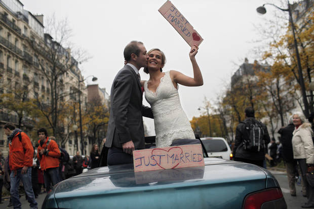 "A bride and a groom stand in a car as they protest against French President Francois Hollande's plan to legalize marriage and adoption for gay people, in Paris, Saturday Nov. 17, 2012. Saturday's event, entitled ""march for everyone"", attracted several thousand people in cities such as Lyon, Marseille and Paris. (AP Photo/Thibault Camus)"