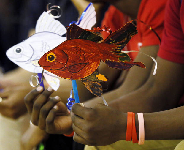 Left: A student holds two paper fish during the assembly Wednesday at John Marshall High School. PHOTOS BY NATE BILLINGS, THE OKLAHOMAN