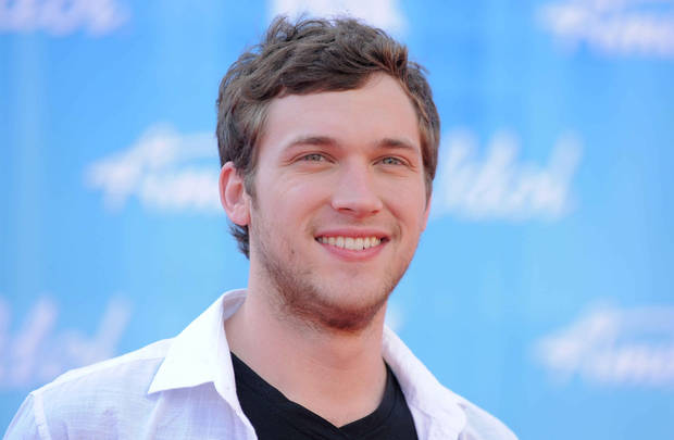In a May 23, 2012 file photo Phillip Phillips arrives at the American Idol Finale on in Los Angeles. Phillips says he wasn't that excited about performing the song �Home� when he won �American Idol� this year. But now, the 21-year-old says he's �starting to grow a connection� to the song, thanks to its use in the 2012 Olympics. �Home� has been used in commercials for the �Fab 5,� the five American female gymnasts who scored gold in the all-around team competition last week. As a result, the song's digitals sales have jumped, selling 228,000 in the last week, a 472 percent increase, according to Nielsen Soundscan. �Home� also leaped 80 spots to No. 9 on the Billboard Hot 100 chart this week. It's sold 844,215 tracks since its June release. (AP Photo by Jordan Strauss/Invision/AP)