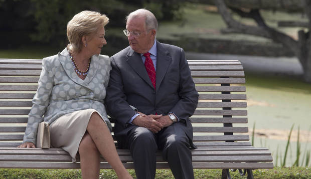 File - In this Sunday, Sept. 2, 2012 file photo, Belgium's King Albert II, right, speaks with Queen Paola as they sit on a bench on the grounds of the Royal Palace in Laeken, Belgium. Albert II�s kingdom is increasingly threatened by royal-bashing separatists seeking the breakup of Belgium. Now, a book dipping deep into the privacy of kings and princes is adding insult to injury. With its back against the wall, the royal palace sought to strike back in the week of Oct. 29, 2012, seeking action against the journalist who published the book ��Royal Questions�� which is sometimes as rich on dangerous liaisons as it is on the use of anonymous sources. (AP Photo/Virginia Mayo, File)