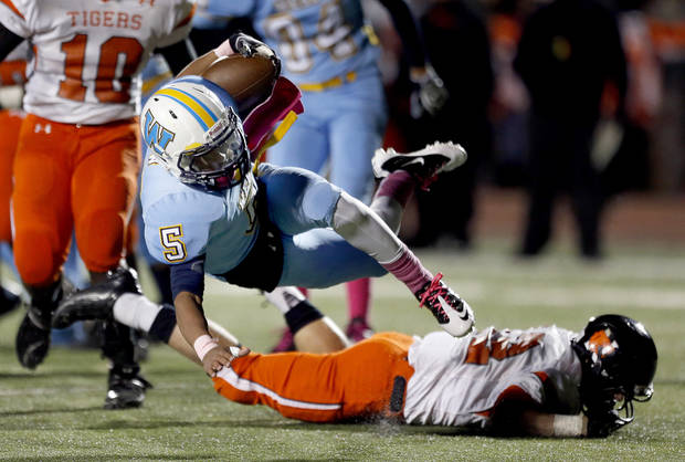 Putnam City West&#039;s Steven Stallings is tripped up by Norman&#039;s Gavin Nadeau during the high school football game between Putnam City West and Norman at Putnam City High School, Thursday, Oct. 25, 2012. Photo by Sarah Phipps, The Oklahoman