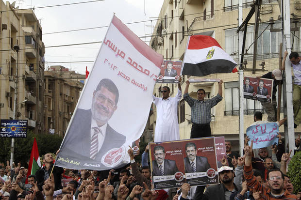 Supporters of Egyptian President Mohammed Morsi chant slogans and wave is campaign posters and a national flag outside the Presidential Palace in Cairo, Egypt, Friday, Nov. 23, 2012. Supporters and opponents of Egypt's Islamist president staged rival rallies Friday after he assumed sweeping new powers, a clear show of the deepening polarization plaguing the country. (AP Photo/Ahmed Gomaa)