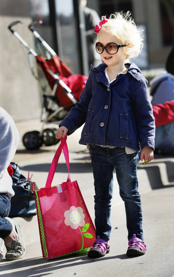 Chloe Horton, 3, wears sunglasses and carries a bag to hold candy as she waits for the 89er Day Parade on Saturday, April 20, 2013 in Norman, Okla.  Photo by Steve Sisney, The Oklahoman