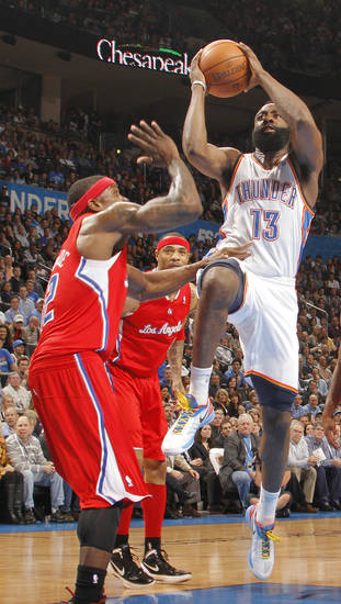 Oklahoma City Thunder guard James Harden (13) shoots the ball over Los Angeles Clippers point guard Eric Bledsoe (12) during the NBA basketball game between the Oklahoma City Thunder and the Los Angeles Clippers at Chesapeake Energy Arena on Wednesday, March 21, 2012 in Oklahoma City, Okla.  Photo by Chris Landsberger, The Oklahoman