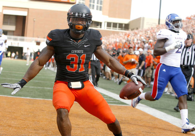 Oklahoma State's Jeremy Smith (31) celebrates a touchdown in front of Kansas' Darius Willis (2) during the first half of the college football game between the Oklahoma State University Cowboys (OSU) and the University of Kansas Jayhawks (KU) at Boone Pickens Stadium in Stillwater, Okla., Saturday, Oct. 8, 2011. Photo by Sarah Phipps, The Oklahoman