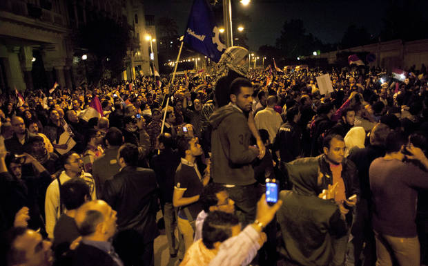 Egyptian protesters chant anti Muslim Brotherhood slogans during a demonstration in front of the presidential palace, in Cairo, Egypt, Tuesday, Dec. 4, 2012. A protest by tens of thousands of Egyptians outside the presidential palace in Cairo turned violent on Tuesday as tensions grew over Islamist President Mohammed Morsi's seizure of nearly unrestricted powers and a draft constitution hurriedly adopted by his allies. (AP Photo/Nasser Nasser)