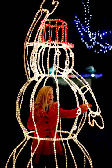 Annie Davis, 9, stands inside a lighted snowman during the Mayor's Tree Lighting at Shannon Miller Park in Edmond. PHOTO BY BRYAN TERRY, THE OKLAHOMAN. <strong>BRYAN TERRY - THE OKLAHOMAN</strong>