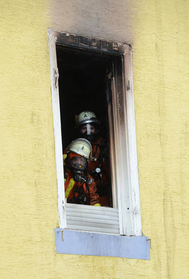 Firefighters look out of the window of a house in  Backnang,  Germany, Sunday March 10, 2013. An early-morning fire on Sunday at the apartment building in southwestern Germany left seven people dead, six of them children, police said. Authorities were alerted to the blaze in Backnang, a town near Stuttgart, at 4.30 a.m. Police said in a statement that they believe the fire broke out in a second-floor apartment, and said that their investigation is focusing on a heater in the apartment.   (AP Photo/dpa, Franziska Kraufmann)