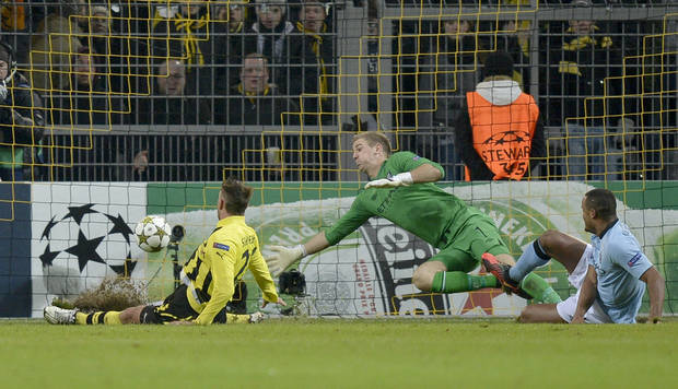 Dortmund's Julian Schieber, left, scores the opening goal against Manchester City goalkeeper Joe Hart, center, and Vincent Kompany, right, during the Champions League Group D soccer match between Borussia Dortmund and Manchester City in Dortmund, Tuesday, Dec. 4, 2012. (AP Photo/Martin Meissner)