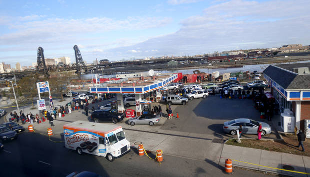 People and vehicles line up at a gas station waiting to fill up, Friday, Nov. 2, 2012, in Newark, N.J. In parts of New York and New Jersey, drivers lined up early Friday for hours at gas stations that were struggling to stay supplied. The power outages and flooding caused by Superstorm Sandy have forced many gas stations to close and disrupted the flow of fuel from refineries to those stations that are open. (AP Photo/Julio Cortez)