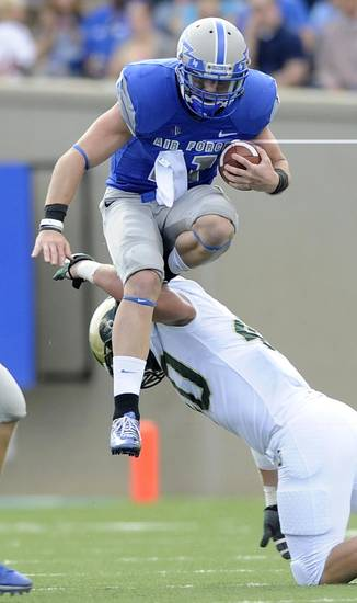 Air Force quarterback Connor Deitz hurdles over Colorado State linebacker Max Morgan during the first half of an NCAA college football game at Falcon Stadium at Air Force Academy, Colo., on Saturday, Sept. 29, 2012. (AP Photo/The Gazette, Jerilee Bennett)