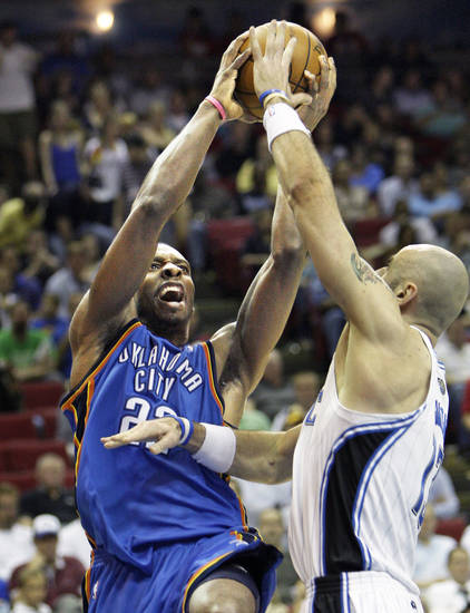 Thunder forward Jeff Green, left, shoots over Magic center Marcin Gortat. AP photo