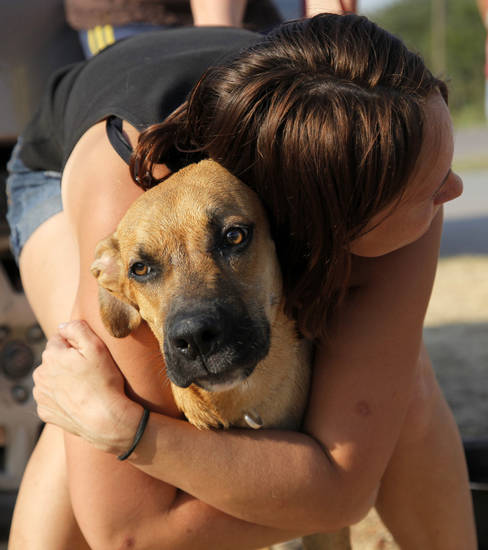 Ruth Hood hugs her dog Punky while waiting a gas station at SE 108th and Hwy 9 after evacuating her home near SE 132nd and Hwy 9 as a wildfire burns through Cleveland County near Norman, Okla., Friday, Aug. 3, 2012. Photo by Nate Billings, The Oklahoman